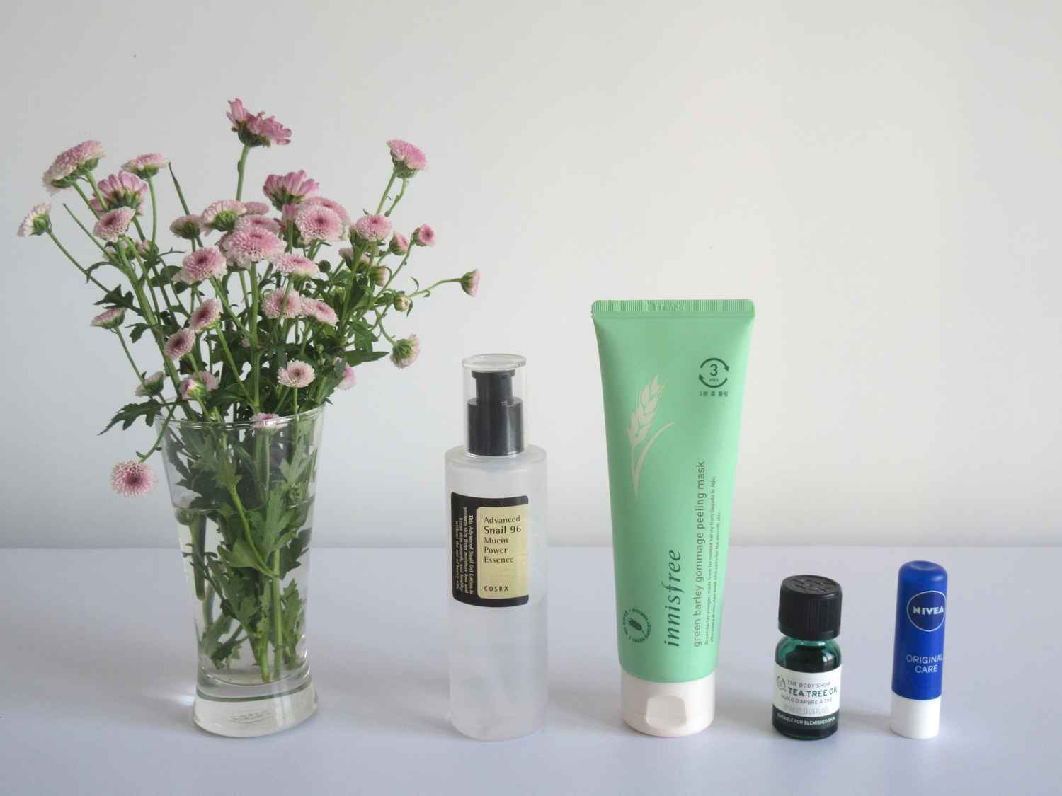 COSRX Advanced Snail 96 Mucin Power Essence, Innisfree Green Barley Gommage Peeling Mask, COSRX Low pH Good Morning Gel Cleanser, The Body Shop's Tea Tree Oil, Nivea's Original Care Lip Balm